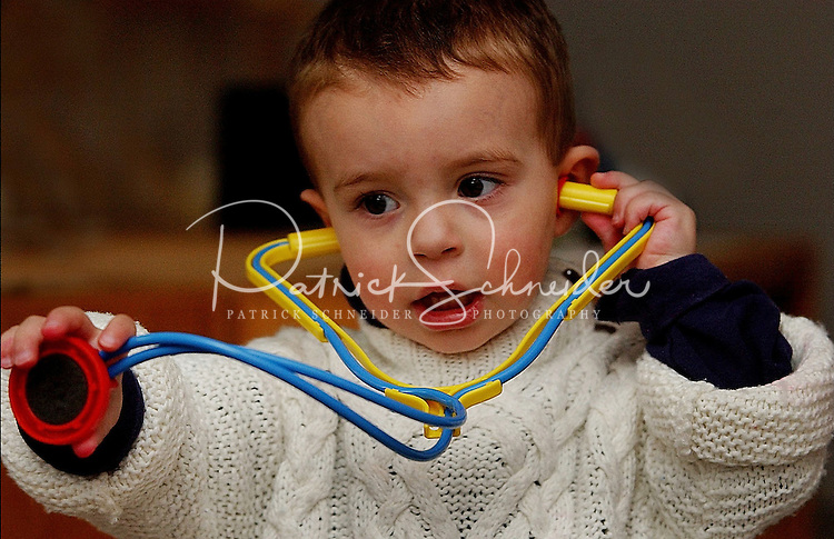 A young boy plays with a toy stethoscope by himself.