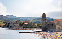 The church Eglise Notre Dame des Anges, our lady of the angels. With its emblematic church tower. The beach in the village. The chateau in Collioure harbour. Collioure. Roussillon. France. Europe. Mountains in the background.