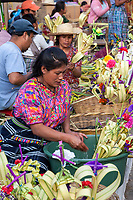 Antigua, Guatemala.  Kaqchikel (Kachiquel) Vendor of Decorations for Palm Sunday Wearing Traditional Blouse (Guipile).