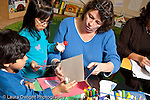 Education preschool 3-4 year olds female teacher working with children on nature art activity gluing leaves to paper horizontal
