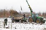 """Foto: VidiPhoto<br /> <br /> HETEREN – Vorig week woensdag zweten bij temperaturen boven de 20 graden Celsius. Deze woensdag een winters tafereel en kleumt personeel van de Combinatie Mauritz op een perceel in het Gelderse Heteren in de sneeuw bij temperaturen rond het vriespunt. Koningslinden worden geladen voor een klant in Oost-Europa. Volgens een woordvoerder van de boomkweker uit Opheusden is """"een witte hoed"""" tijdens werkzaamheden in april wel eens vaker voorgekomen. Werken in de sneeuw, terwijl de prunussen al in bloei staan, is echter geen alledaags gezicht. Bomen met kluit kunnen dankzij de kou nog verplaatst worden. Boomkwekers doen op dit moment goede zaken. Door de lockdown in heel Europa is er veel vraag naar bomen en plantmateriaal omdat mensen nu in hun tuin aan de slag gaan. Ook de Brexit heeft minder problemen opgeleverd dan verwacht."""