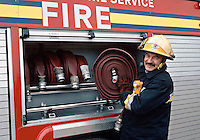 Firefighter collecting Fire Hose from its locker. This image may only be used to portray the subject in a positive manner..©shoutpictures.com..john@shoutpictures.com