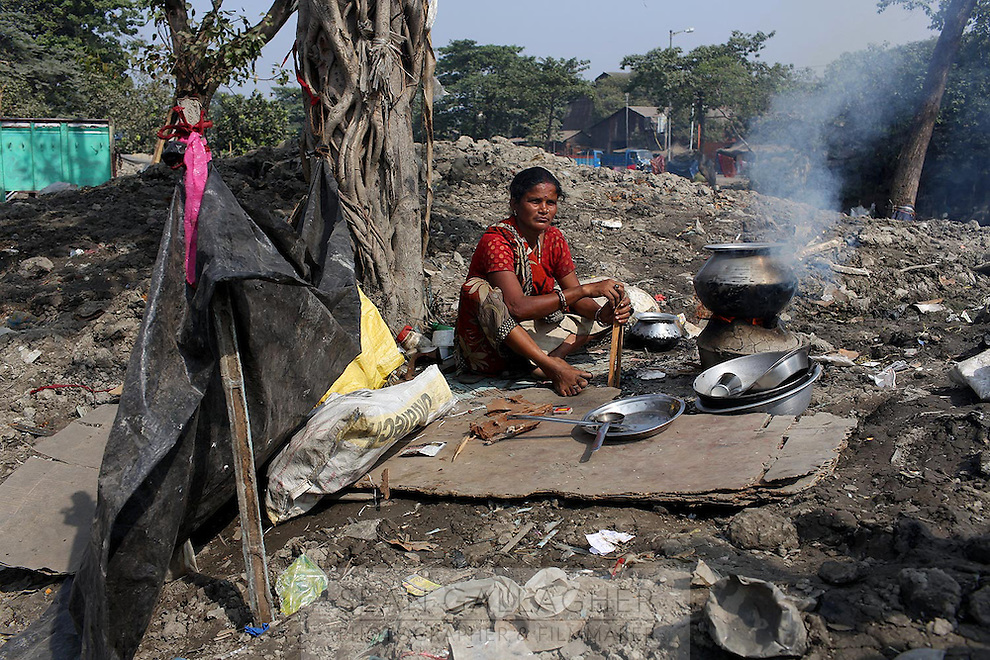 A woman cooks food on the banks of a polluted waterway in central Kolkata.<br /> <br /> To license this image, please contact the National Geographic Creative Collection:<br /> <br /> Image ID: 1925708 <br />  <br /> Email: natgeocreative@ngs.org<br /> <br /> Telephone: 202 857 7537 / Toll Free 800 434 2244<br /> <br /> National Geographic Creative<br /> 1145 17th St NW, Washington DC 20036