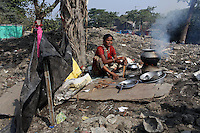 A woman cooks food on the banks of a polluted waterway in central Kolkata.<br />