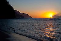 The setting sun casting its golden hue across the Pacific ocean off Ke'e Beach at the foot of Na Pali cliffs, Kauai.