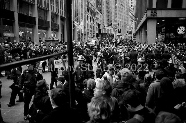 "New York, New York<br /> November 17, 2011<br /> <br /> ""Occupy Wall Street"" protesters mark the movement's two-month milestone by marching from Zuccotti Park, in mass, to various access streets surrounding the New York Stock Exchange, which the police had barricaded off. Yet instead of the police keeping protesters out, protesters locked down those entrances to Wall Street and the New York Stock Exchange creating havoc as the police made more then 240 arrests to try and keep the streets open to normal traffic.<br /> <br /> At Broad Street and Exchange Place, just two blocks from the NYSE, Police try and contain a crowd of anti-Wall Street demonstrators from disrupting business as usual in the financial district. Dozens of arrests are made as protesters do battle with police."