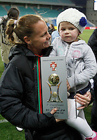 US's Christie Rampone holds the trophy and her daughter after their Algarve Women's Cup soccer match final against Germany at Algarve stadium in Faro, March 13, 2013.  .Paulo Cordeiro/ISI