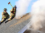 A Hartford firefighter uses an ax to vent the roof as the firefighter behind him radio's their progress to the command post as they straddle the peak of the roof of a 3 story apartment house on Brook Street, Saturday, February 21, 2009, during a two-alarm blaze, all the occupants got out safely. (Jim Michaud/Journal Inquirer)