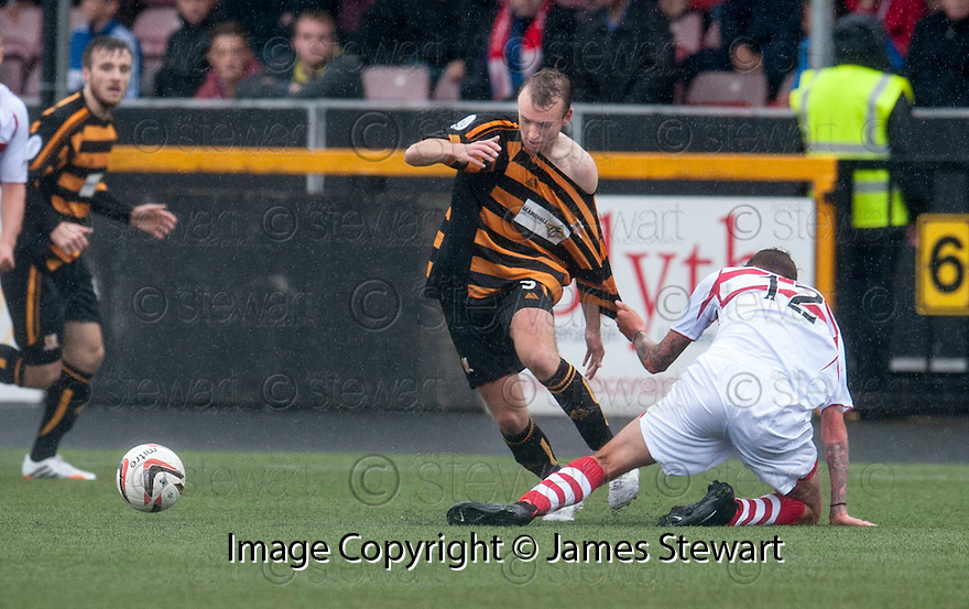 """Stirling's Lewis Coult gets a grip off Alloa""""s Greig Spence."""