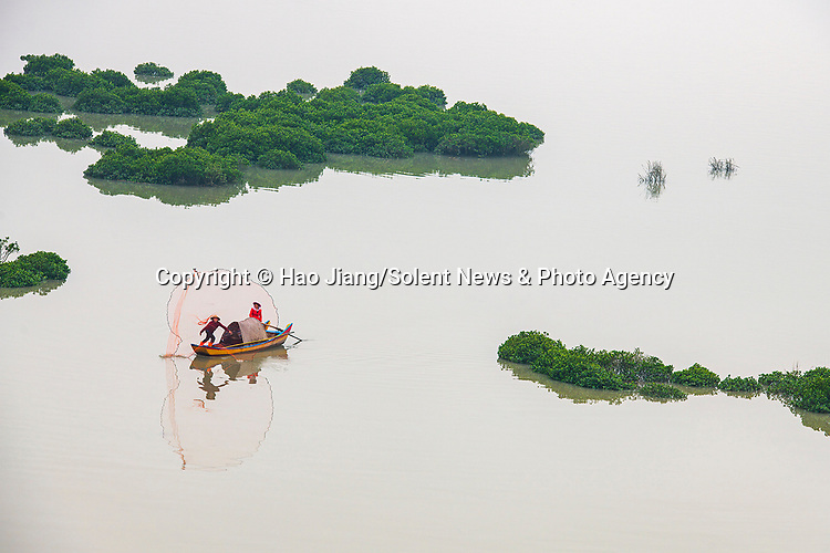 Fishermen navigate their boats through narrow channels of water between mudflats.  The man made mounds are visible in the foggy morning due to a low tide.<br /> <br /> These flats are replicas of others nearby which were used by local fishermen to breed razor clams.  The photos were taken in Xiapu county, in the Fujian province of China, by photographer Hao Jiang.  SEE OUR COPY FOR DETAILS.<br /> <br /> Please byline: Hao Jiang/Solent News<br /> <br /> © Hao Jiang/Solent News & Photo Agency<br /> UK +44 (0) 2380 458800