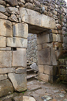 Peru, Machu Picchu.  Inside Main Gate into the City.  The hole in the circulart stone above the door and the chest-high opening on either side served to brace a wooden door as a barrier to entry.