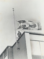 1970 FILE PHOTO - ARCHIVES -<br /> <br /> The flags come down as a security guard in Montreal; atop a public building; lowers both Canadian and Quebec provincial flags to half-staff in mourning for Quebec Labor Minister Pierre Laporte<br /> <br /> 1970<br /> <br /> PHOTO : Graham Bezant - Toronto Star Archives - AQP