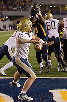 Pitt quarterback Tino Sunseri gets ready to throw the ball as WVU defensive end Bruce Irvin (11) closes in. The WVU Mountaineers beat the Pitt Panthers 21-20 at Mountaineer Field in Morgantown, West Virginia on November 25, 2011.