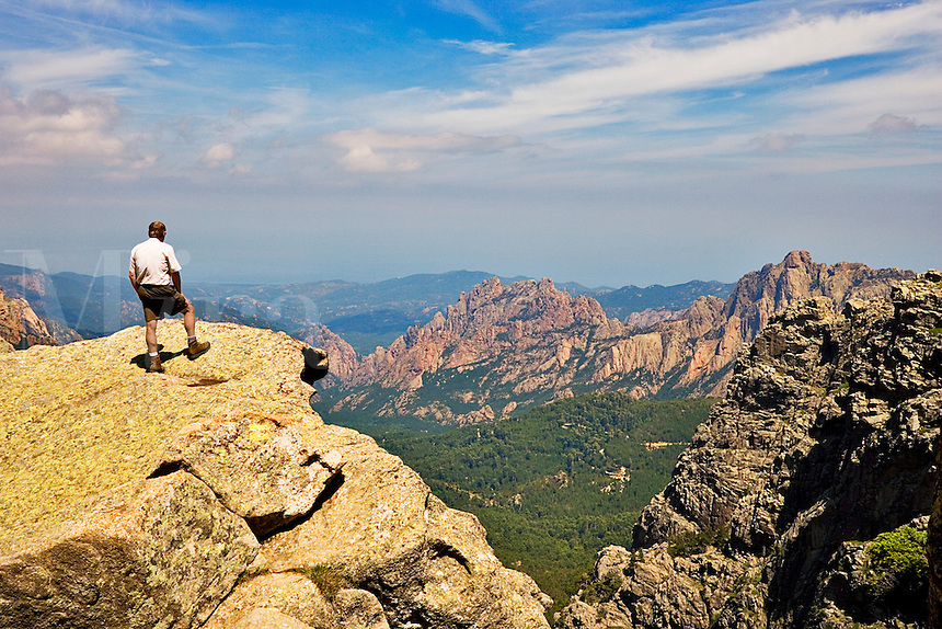 Walker on rocky promontory  amongst summits of Aiguilles de Bavella looking towards Punta di Ferriate and east coast. Corsica. France. Model released.