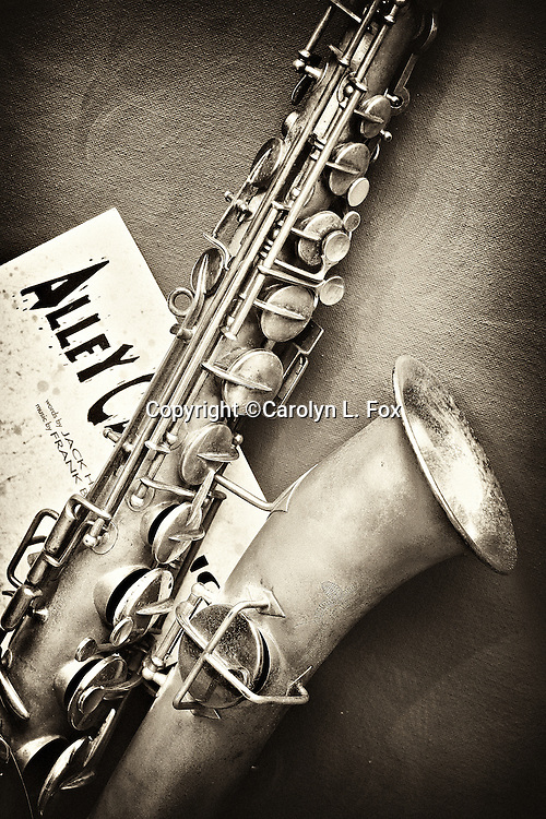 An old melody c saxophone lays with old music.