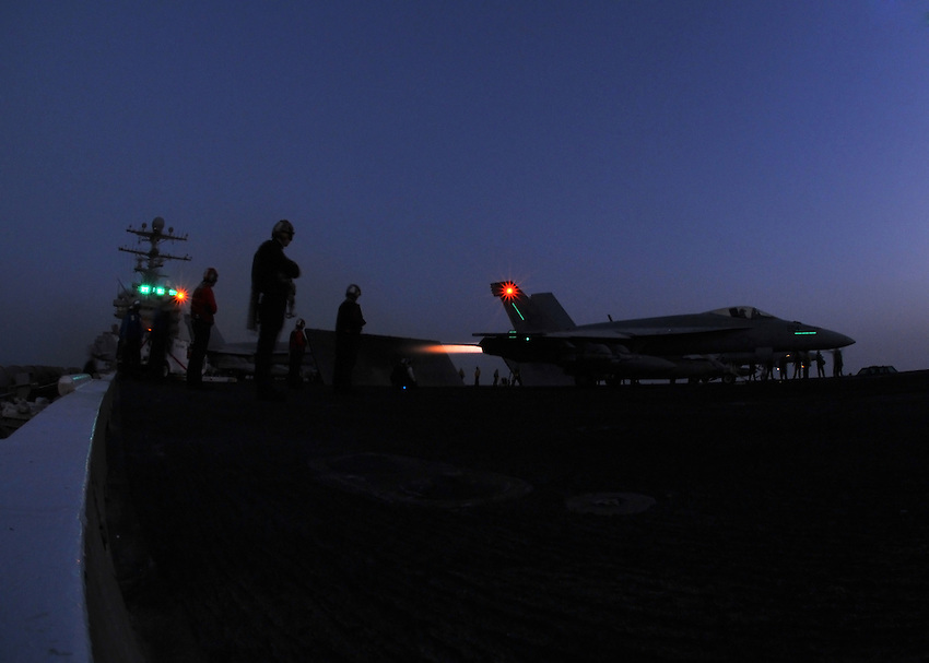 """080608-N-7981E-358 ARABIAN GULF (June 8, 2008)-Squadron personnel stand by while an F/A-18E Super Hornet assigned to """"Kestrels"""" of Strike Fighter Squadron (VFA) 137 revs up its afterburners for launch off the flight deck of Nimitz-class aircraft carrier USS Abraham Lincoln (CVN 72). Lincoln is deployed to the U.S. Navy 5th Fleet area of responsibility to support Maritime Security Operations (MSO).  MSO help develop security in the maritime environment, which promotes stability and global prosperity.  These operations complement the counterterrorism and security efforts of regional nations and seek to disrupt violent extremists' use of the maritime environment as a venue for attack or to transport personnel, weapons or other material.  U.S Navy photo by Mass Communication Specialist 2nd Class James R. Evans (RELEASED)"""