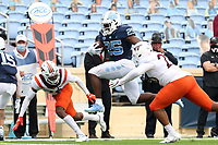 CHAPEL HILL, NC - OCTOBER 10: Javonte Williams #25 of North Carolina lunges over Rayshard Ashby #23 and Jermaine Waller #28 of Virginia Tech on his 19-yard touchdown run during a game between Virginia Tech and North Carolina at Kenan Memorial Stadium on October 10, 2020 in Chapel Hill, North Carolina.
