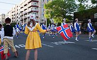 Little girl wearing traditional Norwegian yellow dress waving Norway Flag, 17th of May Parade 2016, Ballard, Seattle, WA, USA.