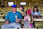 Tom Burns looks over his daughter Delaney's, 10, shoulder as she decides which horses she likes on Black-Eyed Susan Day at Pimlico Race Course in Baltimore, Maryland on May 18, 2012.