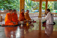 Cambodia, Siem Reap.  Worshiper Seeking Blessing from Buddhist Monks, Preah Ang Chek and Preak Ang Chorm Temple.