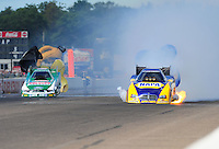 Aug. 20, 2011; Brainerd, MN, USA: NHRA funny car driver Ron Capps (right) has a fire alongside John Force during qualifying for the Lucas Oil Nationals at Brainerd International Raceway. Mandatory Credit: Mark J. Rebilas-