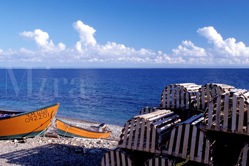 Newfoundland, NF, Canada, Orange fishing boats and lobster traps on the beach at Man Of War Cove on St. George's Bay at Port au Port Peninsula on Gulf of St. Lawrence.