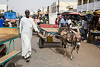 Senegal, Touba.  Street Scene.  The man has a chewing stick in his mouth, for cleaning his teeth.