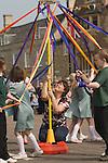 Stilton village May Fair. Primary village school teacher holding up childrens May Pole dancing. Cambridgeshire UK 2008.
