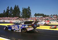 Aug. 3, 2014; Kent, WA, USA; NHRA funny car driver Robert Hight (near lane) races alongside Bob Tasca III during the Northwest Nationals at Pacific Raceways. Mandatory Credit: Mark J. Rebilas-