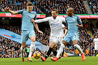 Swansea City's Gylfi Sigurdsson is tackled by Manchester City's John Stones (left) and Manchester City's Fernandinho (right) during the Premier League match between Manchester City and Swansea City at the Etihad Stadium, Manchester, England. Sunday 05 February 2017