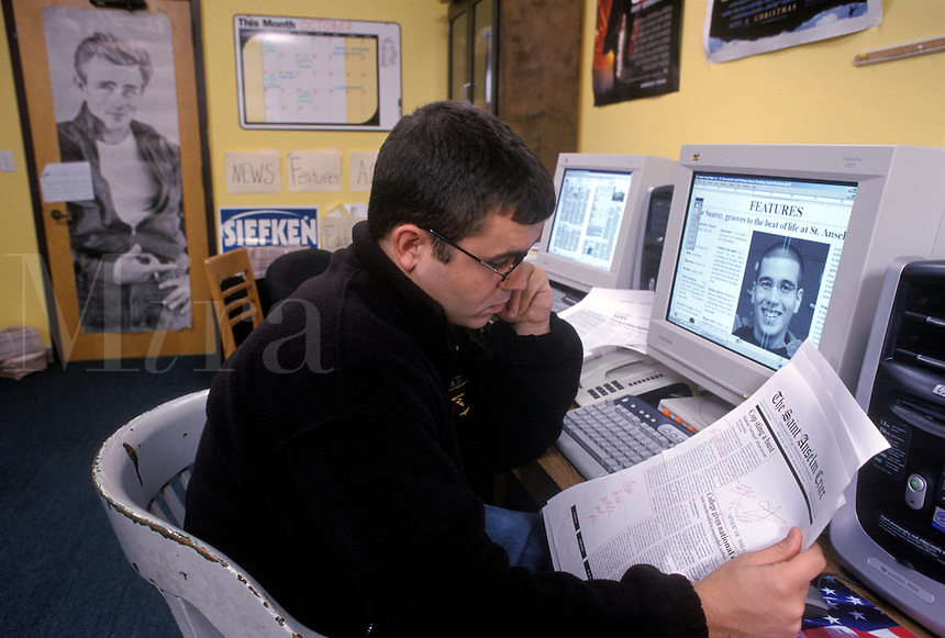 College student working at computer on student newspaper.