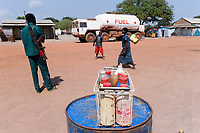 OUTH SUDAN  Bahr al Ghazal region , Lakes State, town Cuibet, fuel tanker and roadside sale of fuels in bottles, soldier with AK-47 machine gun/ SUED-SUDAN  Bahr el Ghazal region , Lakes State, Cuibet, Benzinverkauf an der Strasse, SPLA Soldat mit Kalaschnikow AK 47 und Treibstoff Tankwagen, die Benzin Preise sind durch Inflation und ein Embargo des Nordsudan astronomisch hoch