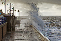 Pictured: A lone man stands to watch the waves crash against the promenade wall in Porthcawl, Wales, UK. Tuesday 01 October 2019<br /> Re: Heavy rain and strong winds caused by Hurricane Lorenzo affect parts of the UK.
