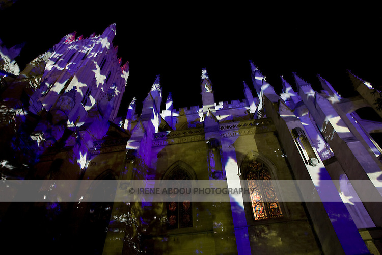 """A stained glass window peeks out from under blue stars, the artistry of Swiss lighting artist Gerry Hofstetter, which pepper the Washington National Cathedral at dusk.  The """"Lighting the Nation, Uniting the World"""" centennial celebration of the Cathedral spotlighted its mission of reconciliation."""