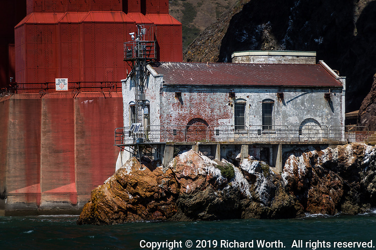 The midday sun casts shadows creating 'frowny faces' on a building at the foot of the Golden Gate Bridge.