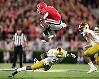ATHENS, GA - SEPTEMBER 21: D'Andre Swift #7 of the Georgia Bulldogs leaps over Shaun Crawford #20 of the Notre Dame Fighting Irish on a run during a game between Notre Dame Fighting Irish and University of Georgia Bulldogs at Sanford Stadium on September 21, 2019 in Athens, Georgia.