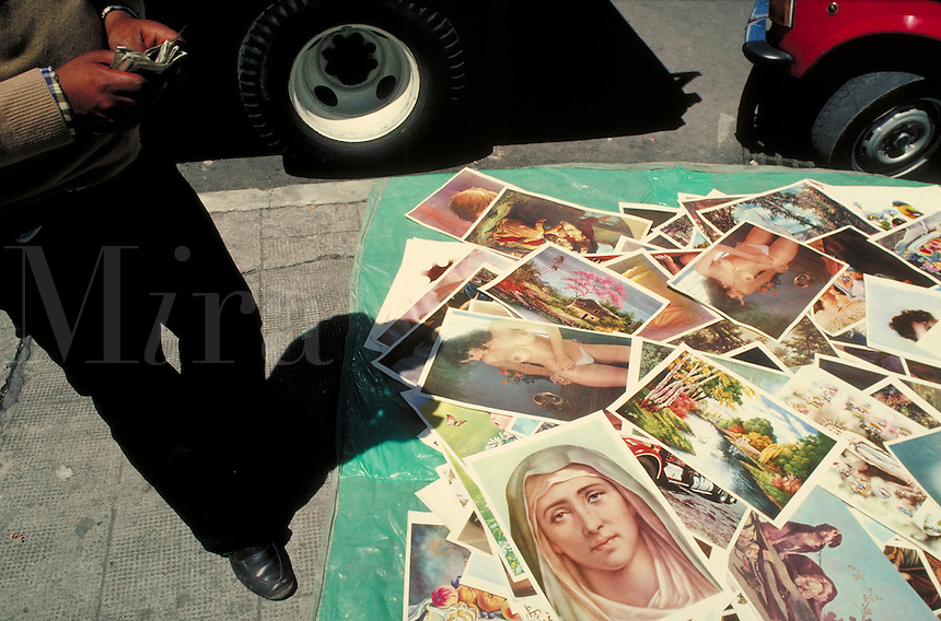 A vendor does a thriving business in laminated pictures on the streets of Quito, Ecuador. Quito, Ecuador.