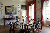 The dining room is furnished with a circular pedestal table and the walls are decorated with carvings by Grinling Gibbons