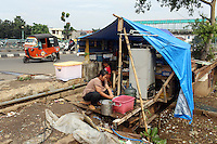 A woman cleans plates in a small makeshift restaurant at the side of a road in central Jakarta.
