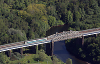 Aerial view of an Arriva train travelling on a bridge over river Tawe