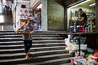 A restaurant worker takes lunch to a stall in a market off Shaanxi Road in Yuzhong District, Chongqing, China.