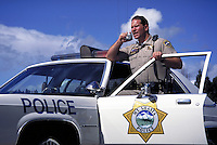 Police officer standing by patrol car using radio. Police, law enforcement, peace officer, communications, law and order, safety, response. policeman. Mt. Shasta CA USA outdoors.
