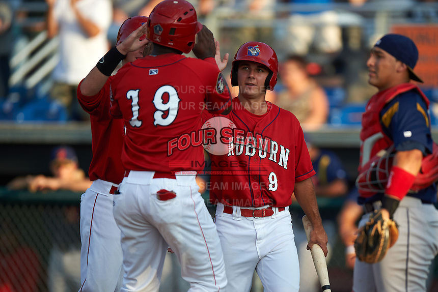 Auburn Doubledays outfielder Randy Encarnacion (19) high fives teammates Matthew Page (15) and Max Schrock (9) after hitting a home run during a game against the State College Spikes on July 6, 2015 at Falcon Park in Auburn, New York.  State College defeated Auburn 9-7.  (Mike Janes/Four Seam Images)