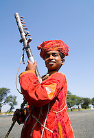 Young boy aged 10 with musical instrument called Sarangi on road to Jodhpur in Rajasthan India