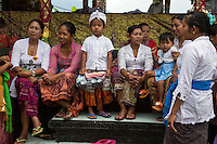 Jatiluwih, Bali, Indonesia.  Balinese Women and Children Waiting for a Ceremony to Begin at the Luhur Bhujangga Waisnawa Hindu Temple.  The little boy is wearing a sarong and an udeng, the traditional male head cloth.