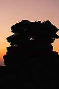 The silhouette of a rock cairn on the summit of Mount Washington at dusk in the White Mountains, New Hampshire USA.