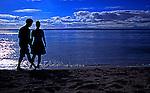 Couple walks romantically along the beach at Golden Gardens park, a Seattle City Park, Washington.