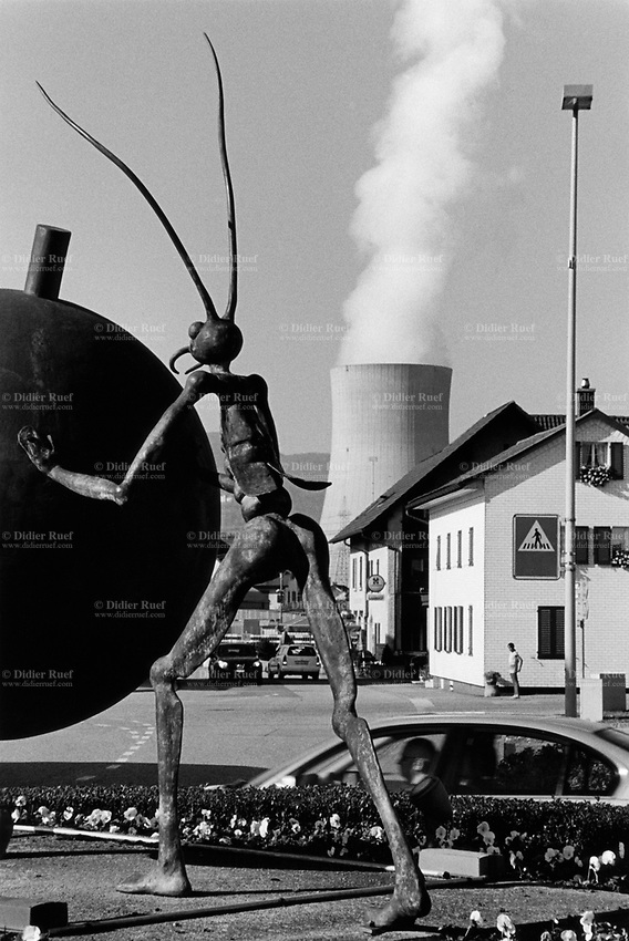 Switzerland. Canton Solothurn. Däniken. Däniken is a municipality in the district of Olten. Cars on the road and pedestrians on sidewalks. A bronze sculpture by the artist Oliviero Gorza stands in the middle of a road circle. In the back, the Gösgen Nuclear Power Plant (in German Kernkraftwerk Gösgen, abbreviated in KKG) is located on a loop of the Aar river. It is operated by the ad hoc society Kernkraftwerk Gösgen-Däniken AG. A roundabout, also called a traffic circle, road circle, rotary, rotunda or island, is a type of circular intersection or junction in which road traffic flows almost continuously in one direction around a central island. 18.10.17  © 2017 Didier Ruef