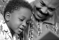 African-American son showing father computer; learning; family activities, parents, children, Black child, man, computers, smiling, black and white image. Dave Johnson, Gus Hoffman.