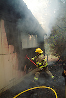 Fire fighters from several agencies fight a structure fire on Dupont Road in Occidental, California, USA.